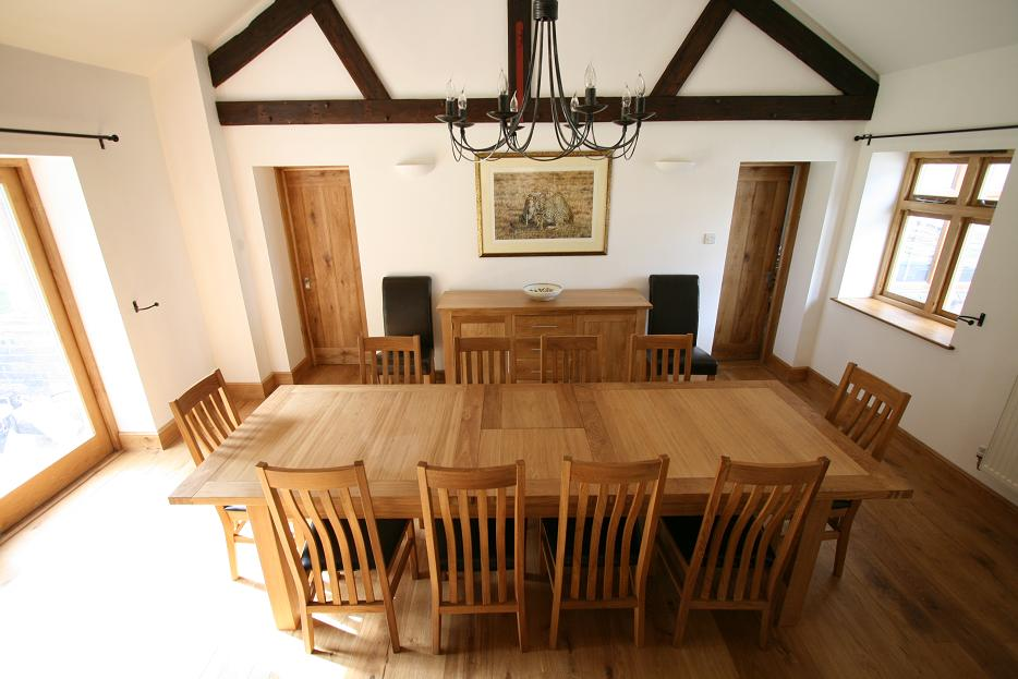 The 2.4   2.9m Tallinn Butterfly Extending European Oak Table Shown With 10  Stunning Winchester Leather Chairs With Dark Brown Pads. Priced At £1629.